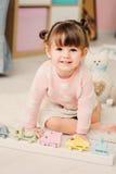 Nette glückliche 2 Jahre alte Baby, die zu Hause mit Spielwaren spielen Stockfotos