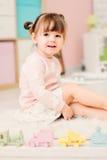 Nette glückliche 2 Jahre alte Baby, die zu Hause mit Spielwaren spielen Lizenzfreies Stockbild
