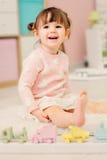 Nette glückliche 2 Jahre alte Baby, die zu Hause mit Spielwaren spielen Stockfotografie
