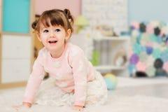 Nette glückliche 2 Jahre alte Baby, die zu Hause mit Spielwaren spielen Stockfoto