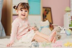 Nette glückliche 2 Jahre alte Baby, die zu Hause mit Spielwaren spielen Lizenzfreie Stockbilder