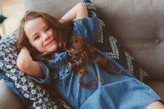 nette glückliche 5 Jahre alte Kindermädchen, die sich allein zu Hause entspannen Stockfotografie