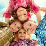 Nette glückliche Kinder, die unten schauen und Händchenhalten Stockbilder