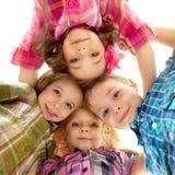 Nette glückliche Kinder, die unten schauen und Händchenhalten Stockfoto