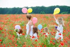 Nette glückliche Kinder mit ihren Müttern, die auf Sommerfeld gehen lizenzfreies stockbild