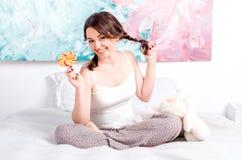 Nette, glückliche Pyjamas des jungen Mädchens zu Hause mit umsponnenen Zöpfen Stockfotos