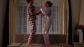 Nette glückliche Schwesterzwillinge in den pajams, die auf die Couch in einem gemütlichen Wohnzimmer springen und Spaß wie in Kin stock video