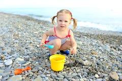 Nette glückliche Spiele des kleinen Mädchens auf dem Strand stockbild