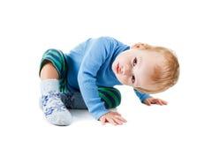 Nette glückliche Babyblondine in einer blauen Strickjacke, die auf weißem Hintergrund spielt und lächelt Lizenzfreie Stockfotografie