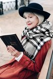 Nette grau-haarige Frau, die religiöse Literatur lesend genießt lizenzfreie stockbilder