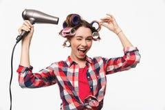 Nette Hausfrau mit Lockenwicklern in der Haarstellung stockbild