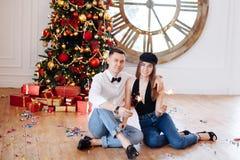 Nette intelligente Paare mit der Wunderkerze, die zu Hause nahe verziertem Weihnachtsbaum vor Partei flirtet stockfoto