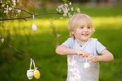 Nette Jagden des kleinen Jungen für Osterei auf Niederlassung des blühenden Baums stockfotos