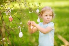 Nette Jagden des kleinen Mädchens für Osterei auf blühendem Baum der Niederlassung stockbilder