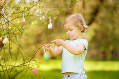 Nette Jagden des kleinen Mädchens für Osterei auf blühendem Baum der Niederlassung lizenzfreies stockfoto