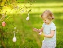Nette Jagden des kleinen Mädchens für Osterei auf blühendem Baum der Niederlassung stockfotos