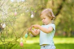 Nette Jagden des kleinen M?dchens f?r Osterei auf bl?hendem Baum der Niederlassung stockfotografie
