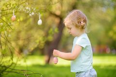 Nette Jagden des kleinen M?dchens f?r Osterei auf bl?hendem Baum der Niederlassung stockfotos