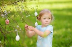 Nette Jagden des kleinen M?dchens f?r Osterei auf bl?hendem Baum der Niederlassung lizenzfreie stockfotografie
