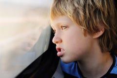 Nette 7 Jahre alte Junge, die durch das Fenster schauen Lizenzfreie Stockbilder