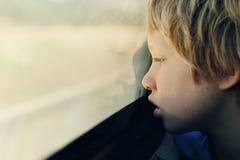 Nette 7 Jahre alte Junge, die durch das Fenster schauen Stockfoto