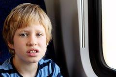 Nette 7 Jahre alte Junge, die durch das Fenster schauen Stockbild