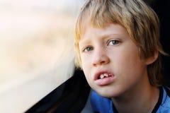 Nette 7 Jahre alte Junge, die durch das Fenster schauen Lizenzfreies Stockfoto