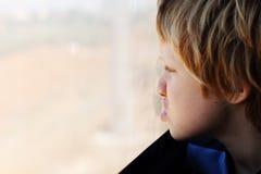 Nette 7 Jahre alte Junge, die durch das Fenster schauen Lizenzfreies Stockbild