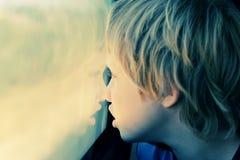 Nette 7 Jahre alte Junge, die durch das Fenster schauen Lizenzfreie Stockfotos