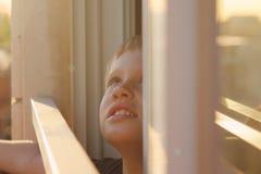 Nette 7 Jahre alte Junge, die heraus das Fenster schauen Lizenzfreies Stockbild