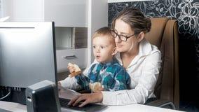 Nette 2 Jahre alte Junge, die im Büro mit seiner Mutter sitzen Stockfotografie
