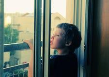 Nette 7 Jahre alte Junge schaut heraus das Fenster Stockfotos