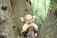 Nette 2 Jahre alte Mädchen, die mit ihrem Hund spielen Stockfotografie