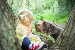 Nette 2 Jahre alte Mädchen, die mit ihrem Hund spielen Stockbild