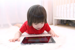 Nette 2 Jahre Junge im roten T-Shirt mit Tablet-Computer zu Hause Stockfoto
