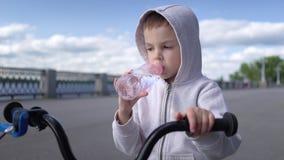 Nette 3 - 4 Jahre Jungenkind, die lernen, erstes laufendes Balancenfahrrad und Getränkwasser zu reiten stock video