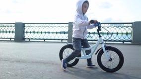 Nette 3 - 4 Jahre Jungenkind, die lernen, erstes laufendes Balancenfahrrad zu reiten stock video footage