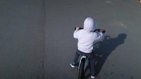 Nette 3 - 4 Jahre Jungenkind, die lernen, erstes laufendes Balancenfahrrad zu reiten stock footage