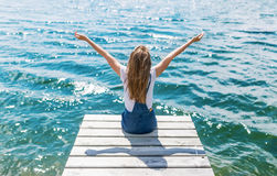 Nette joyfull Jugendliche, die auf kleinem Dock sitzt und den Fluss betrachtet stockbild