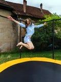 Nette Jugendliche, die auf Trampoline springt lizenzfreie stockfotografie