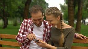 Nette jugendliche Tochter, die lustiges Video auf Mobiltelefon zeigt, um hervorzubringen, im Park sich entspannen stock footage