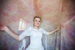 Nette junge blonde Braut, die unter langen Vorhängen auf einem backgr aufwirft Stockbild