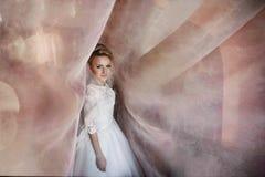Nette junge blonde Braut, die unter langen Vorhängen auf einem backgr aufwirft Lizenzfreie Stockfotografie