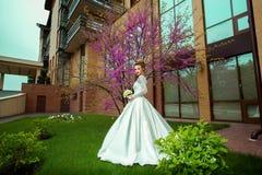 Nette junge blonde Braut im Hochzeitskleid, welches draußen die Kamera im fron von Kirschblüte-Baum betrachtet Stockbild