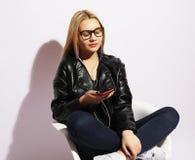 Nette junge blonde Frau, die auf dem Stuhl und dem Gebrauch Smartphone über weißem Hintergrund sitzt Stockbild
