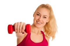 Nette junge blonde Frau, die in der Eignungsturnhalle vorbei lokalisiert ausarbeitet Stockfotos