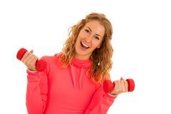 Nette junge blonde Frau, die in der Eignungsturnhalle vorbei lokalisiert ausarbeitet Lizenzfreie Stockfotos