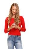 Nette junge blonde Frau, die ein SMS auf Mobile liest Stockfoto