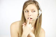Nette junge blonde Frau mit den Kopfhörern, die Anruf beantworten Stockfotografie