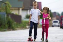 Nette junge blonde Kinder, Bruder und Schwester, Mädchen im rosa Klumpen Stockfotografie